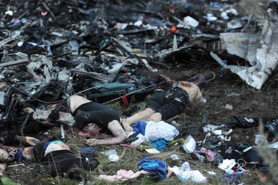 A picture taken on July 17, 2014 shows bodies amongst the wreckages of the malaysian airliner carrying 295 people from Amsterdam to Kuala Lumpur after it crashed, near the town of Shaktarsk, in rebel-held east Ukraine. Pro-Russian rebels fighting central Kiev authorities claimed on Thursday that the Malaysian airline that crashed in Ukraine had been shot down by a Ukrainian jet. AFP PHOTO/DOMINIQUE FAGET