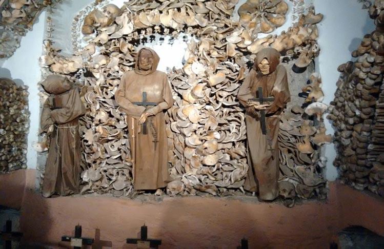 Tres hermanos Capuchinos rodeados de pelvis en otra de las capillas de la Cripta.