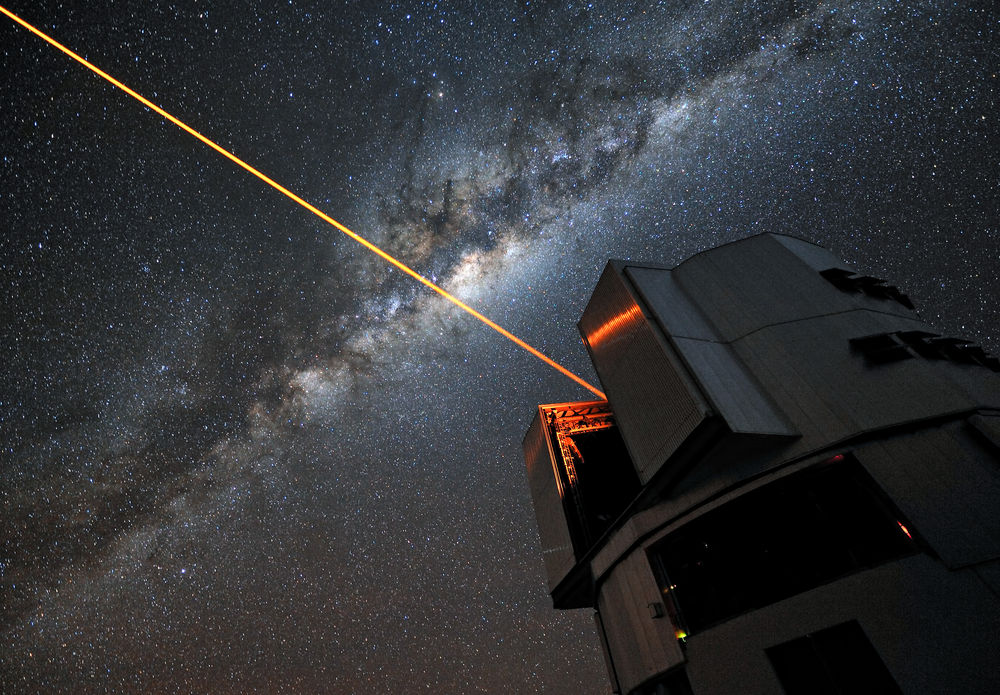 "A glowing laser shines forth from the European Southern Observatory's Very Large Telescope. Piercing the dark Chilean skies, its mission is to help astronomers explore the far reaches of the cosmos. ESO Photo Ambassador Gerhard Hüdepohl was on hand to capture the moment in a stunning portrait of modern science in action.  We have all gazed up at the night sky and seen the stars gently twinkle as the Earth's turbulent atmosphere causes their light to shimmer. This is undoubtedly a beautiful sight, but it causes problems for astronomers, who want the crispest possible views. To help them achieve this, professional stargazers use something that sounds as though it has come from science fiction: a laser guide star that creates an artificial star 90 km above the surface of the Earth. The method by which it achieves this is nothing short of remarkable. The laser energises sodium atoms high in the Earth's mesosphere, causing them to glow and creating a bright dot that to observers on the ground appears to be a man-made star. Observations of how this ""star"" twinkles are fed into the Very Large Telescope's adaptive optics system, controlling a deformable mirror in the telescope to restore the image of the star to a sharp point. By doing this, the system also compensates for the distorting effect of the atmosphere in the region around the artificial star. The end result is an exceptionally crisp view of the sky, allowing ESO astronomers to make stunning observations of the Universe, almost as though the VLT were above the atmosphere in space. Links Adaptive Optics and the Laser Guide Star: http://www.eso.org/public/teles-instr/technology/adaptive_optics.html ESO Photo Ambassadors"